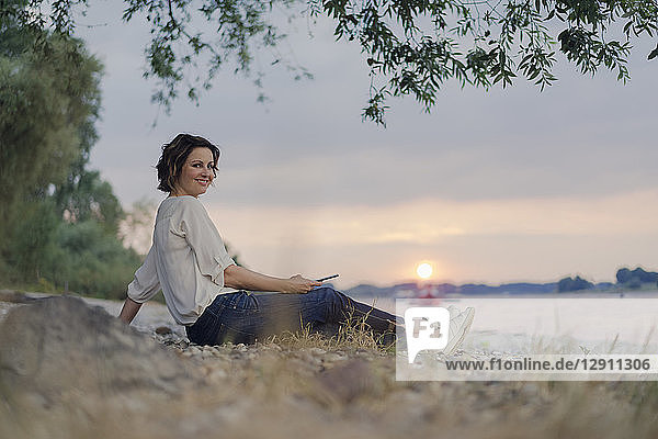Woman sitting at the river  watching sunset