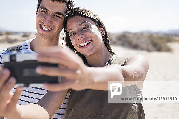 Young couple having fun on the beach  taking smartphone selfies