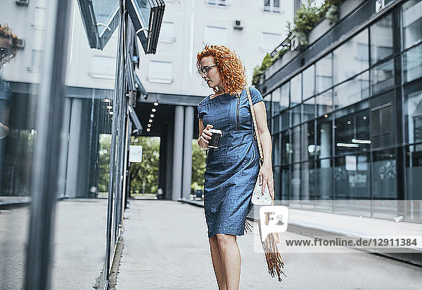 Young businesswoman window shopping in the city  carrying take out coffee