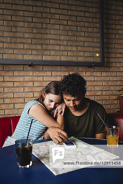 Affectionate young couple sitting at table in a cafe with map and cell phone