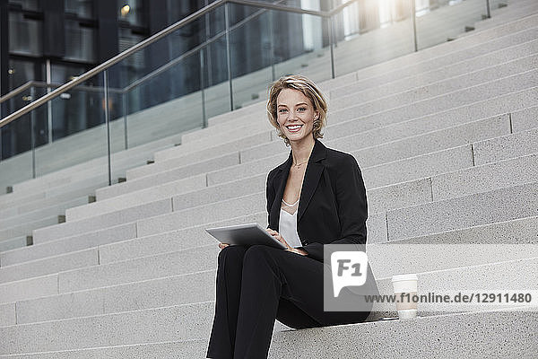 Portrait of smiling businesswoman with tablet and coffee to go sitting on stairs outdoors