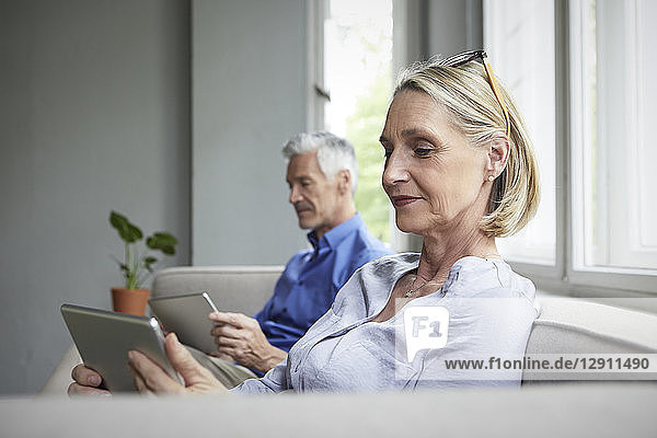 Mature couple sitting on couch at home using tablets