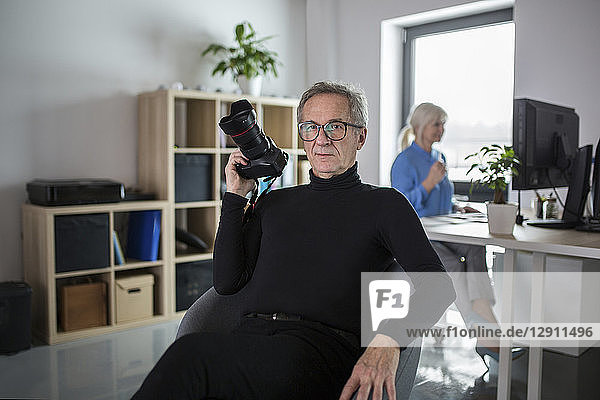 Senior man with camera sitting in office with colleague working behind him