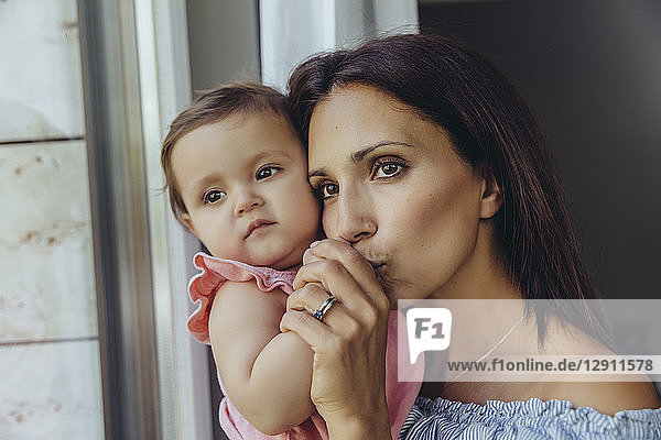 Mother looking out of window with baby daughter at home