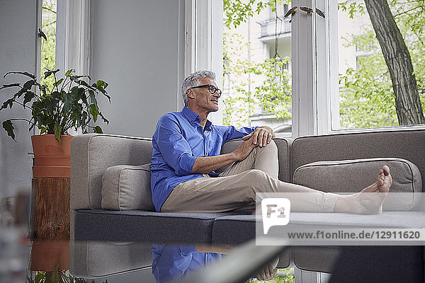 Mature man sitting on couch at home