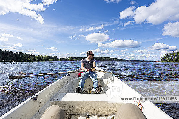 Finland  Man rowing in a boat on a lake