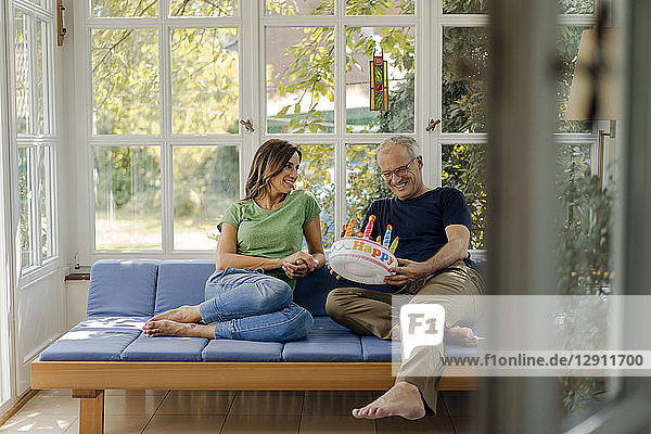 Happy mature couple sitting on couch at home with fake birthday cake