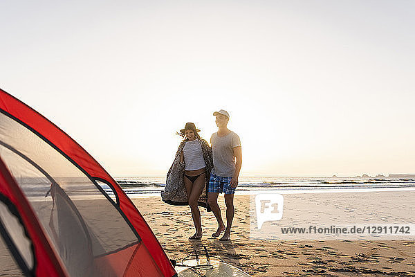 Romantic couple camping on the beach  doing a beach stroll at sunset