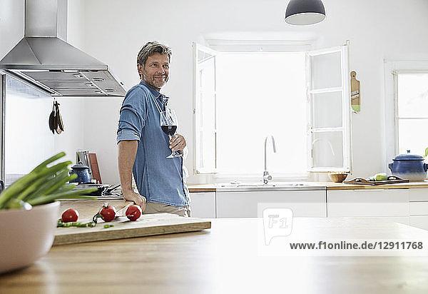 Mature man in his kitchen drinking red wine
