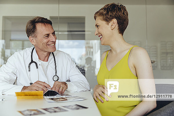 Pregnant woman discussing ultrasonic scans with her doctor