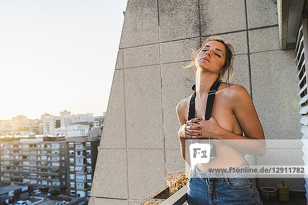 Topless young woman with camera standing on balcony