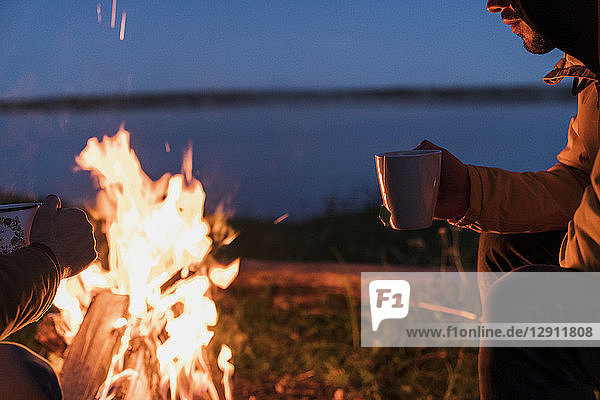 Young man sitting at a campfire  watching the flames