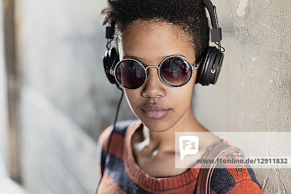 Portrait of young woman wearing sunglasses listening music with headphones