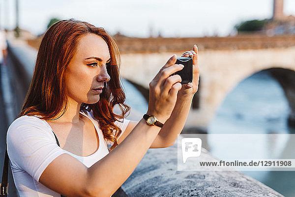 Italy  Verona  redheaded woman taking photo with smartphone