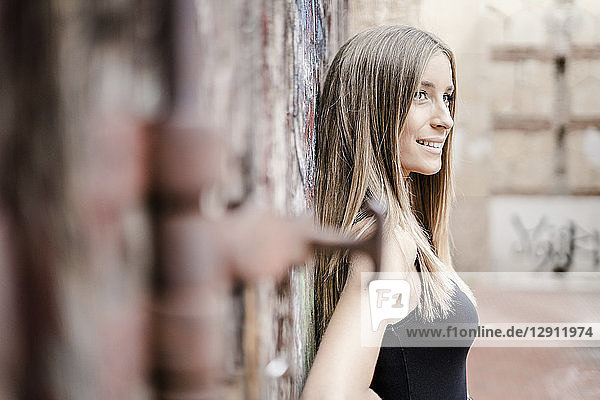 Smiling teenage girl leaning at a wall