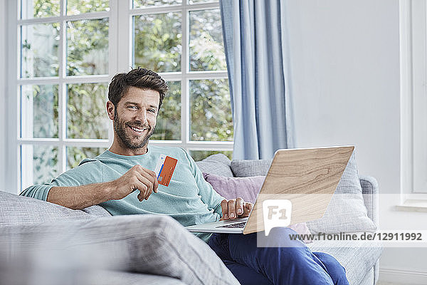 Portrait of smiling man at home shopping online