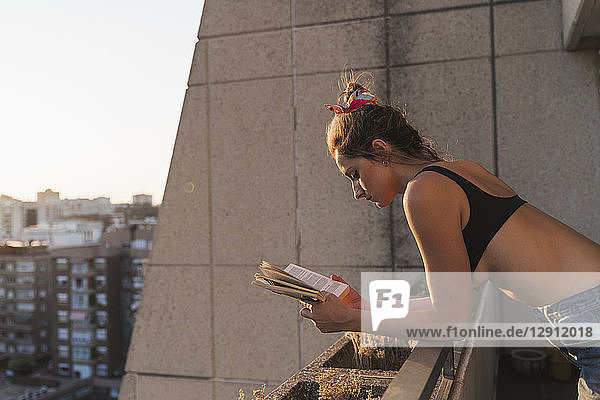 Young woman wearing bra reading book on balcony