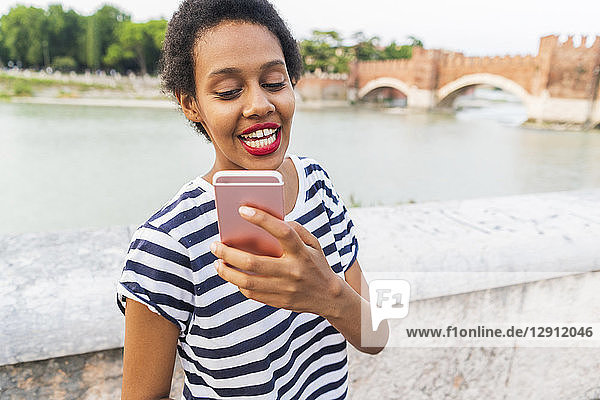 Smiling young woman using cell phone at the riverside