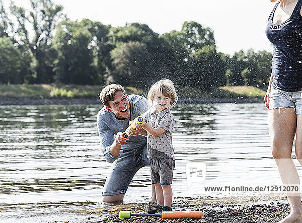 Father and son having fun at the riverside  playing with a water gun
