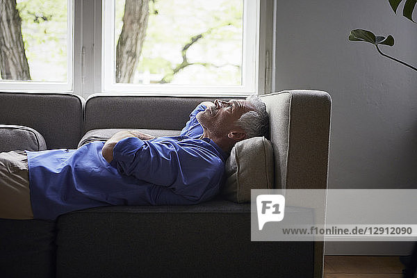Mature man lying on couch at home