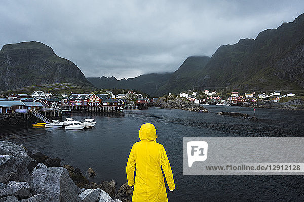 Norway  Lofoten  rear view of man standing in a fishing village at the coast