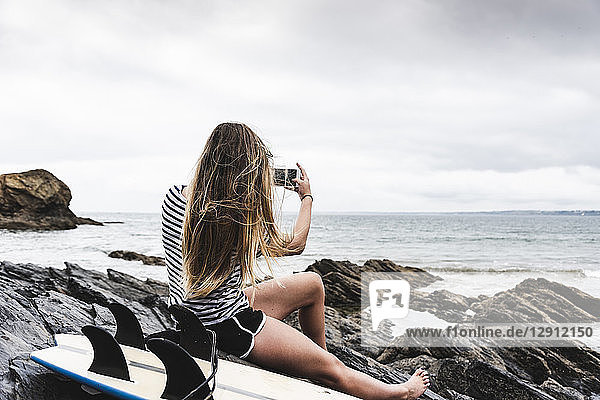 Young woman with surfboard sitting on the beach  using smartphone