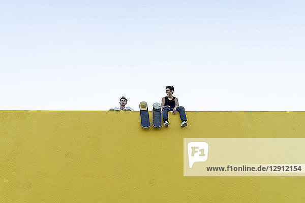 Two young men with skateboards at a high yellow wall