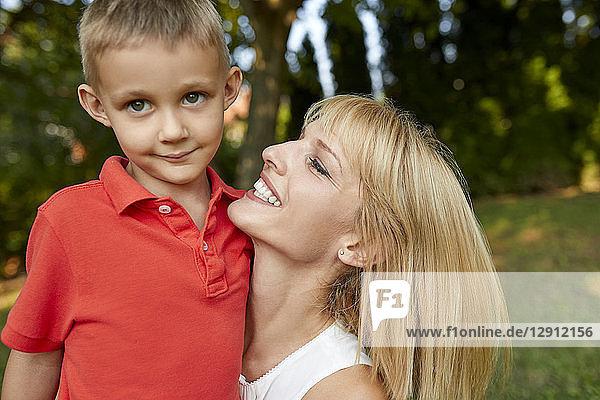 Happy mother carrying her son in garden