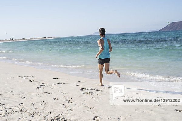 Spain  Canary Islands  Fuerteventura  rear view of young man running on the beach