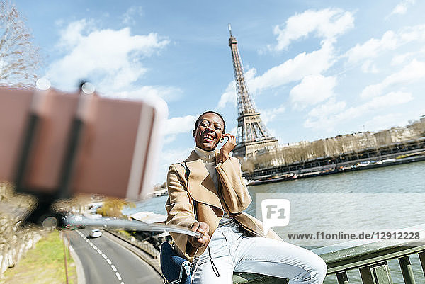 France  Paris  Woman sitting on bridge over the river Seine with the Eiffel tower in the background taking a selfie