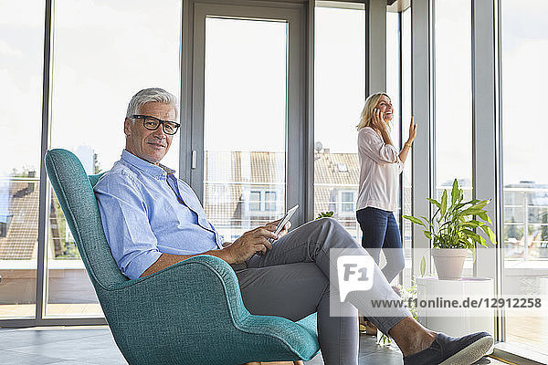 Mature couple relaxing at home using tablet and cell phone