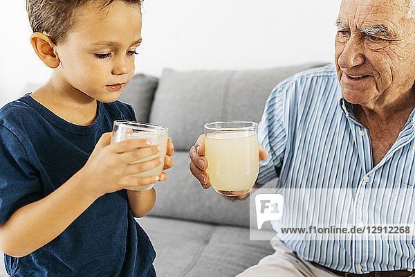 Grandfather and grandson drinking lemonade at home