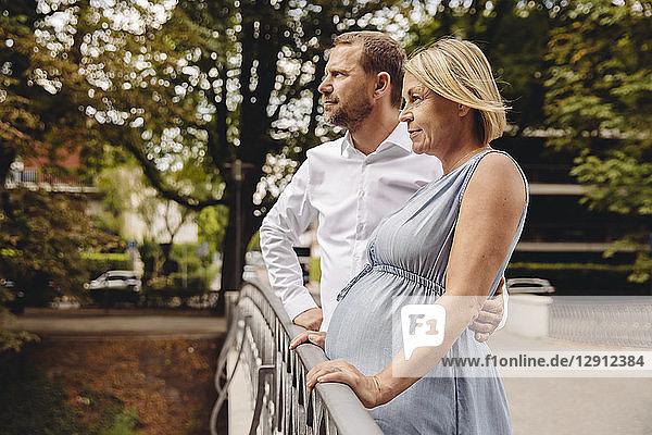 Mature pregnant couple standing at bridge in park