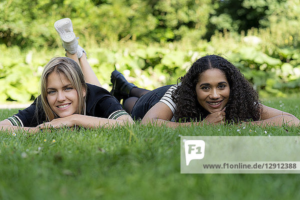 Two girlfriends relaxing in grass in a park
