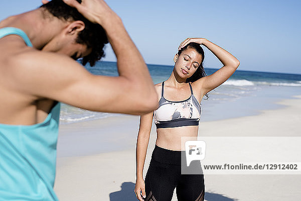 Spain  Canary Islands  Fuerteventura  young womand and young man exercising on the beach