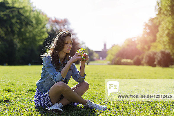 Young woman sitting in a park holding flowers