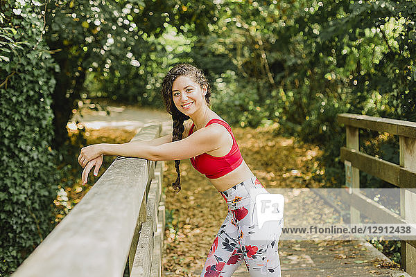 Young woman smiling during break  after practicing Pilates in an urban park