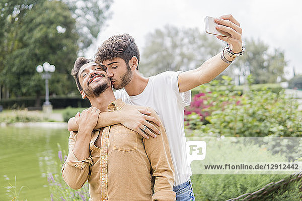 Happy young gay couple taking selfie with smartphone at city park