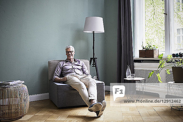 Portrait of smiling mature man sitting on armchair at home