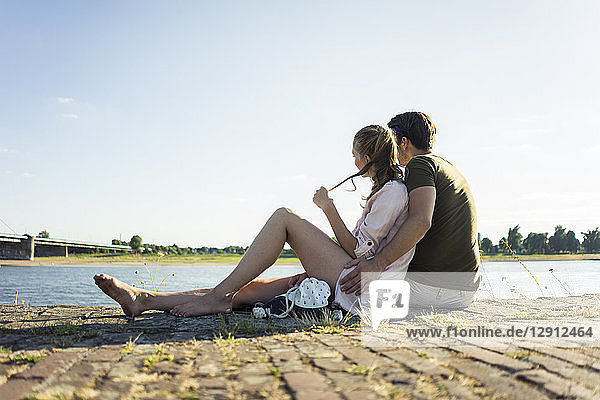 Couple relaxing at the riverside in summer