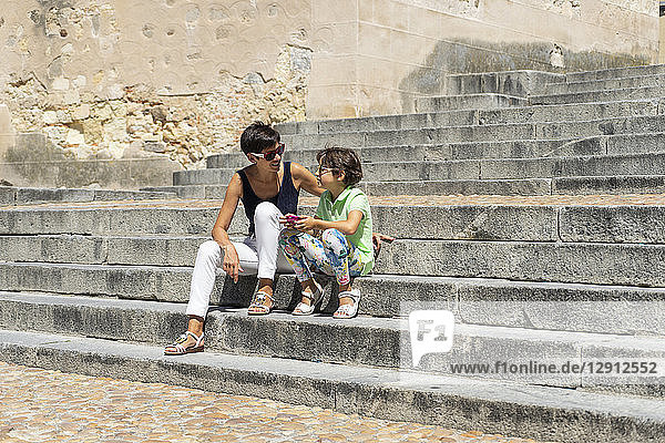 Spain  Castile and Leon  Segovia  Mother and daughter sitting on stairs