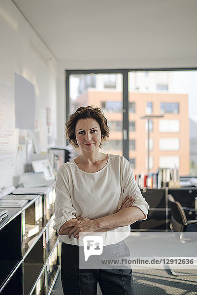 Successful businesswoman standing in her office with arms crossed
