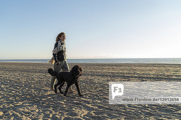 Young woman walking on the beach with her dog