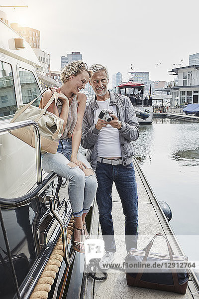 Older man with camera and young woman standing with travelling bags on jetty next to yacht