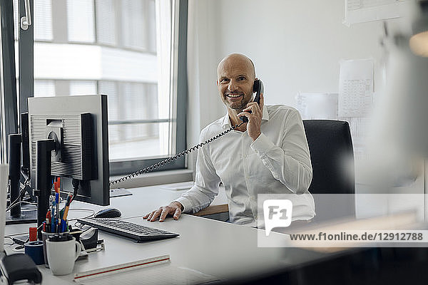 Smiling businessman sitting at his desk  talking on the phone