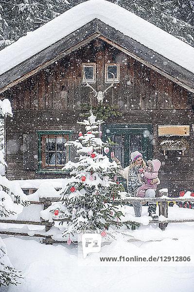 Austria  Altenmarkt-Zauchensee  mother with little son decorating Christmas tree at wooden house