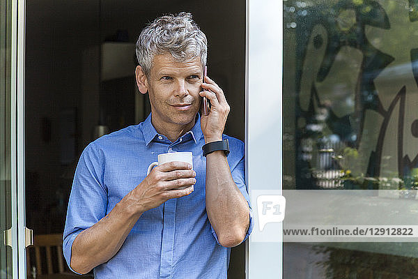 Portrait of mature man on the phone leaning agaich door case with coffee mug