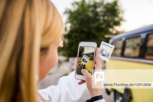 Young woman taking cell phone picture of instant photo at a van