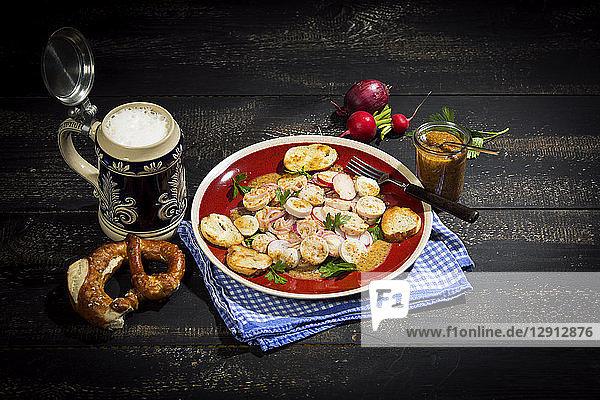 Bavarian veal sausage salad with roasted pretzel rolls  sweet mustard  pretzels  red radish and beer mug