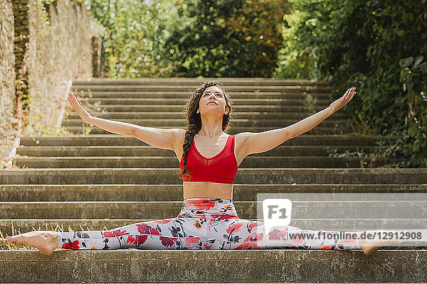 Young woman practicing Pilates in an urban park  spagat on steps